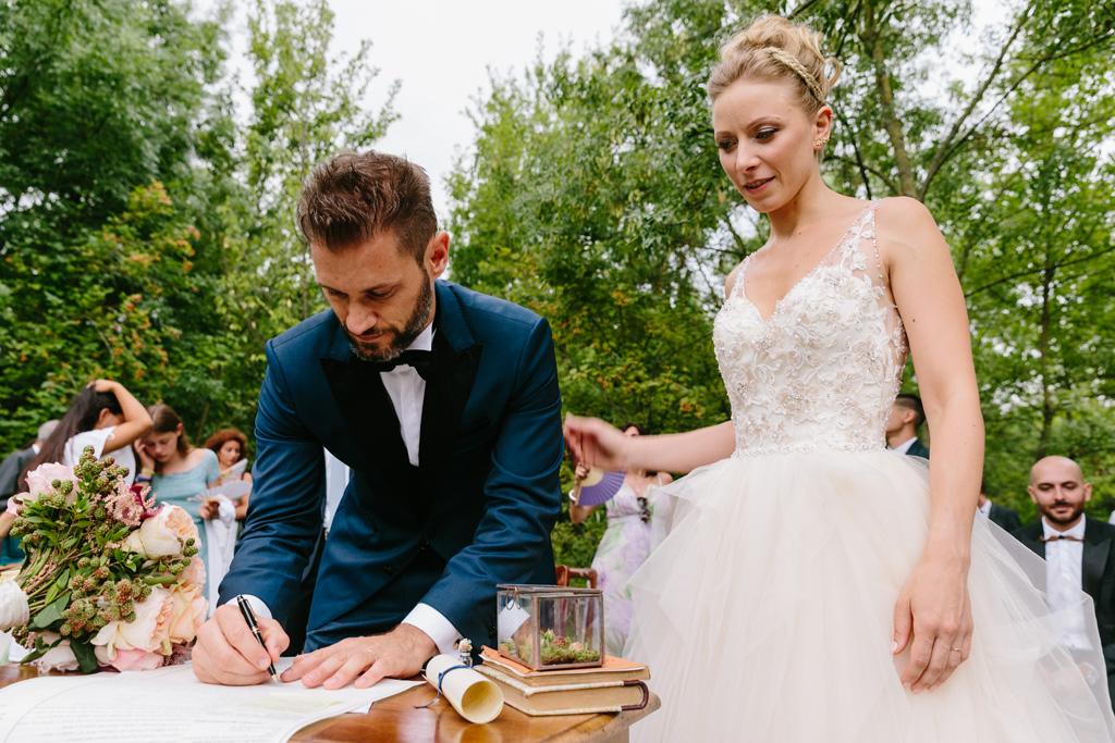 Lo sposo firma le carte per ufficializzare il matrimonio