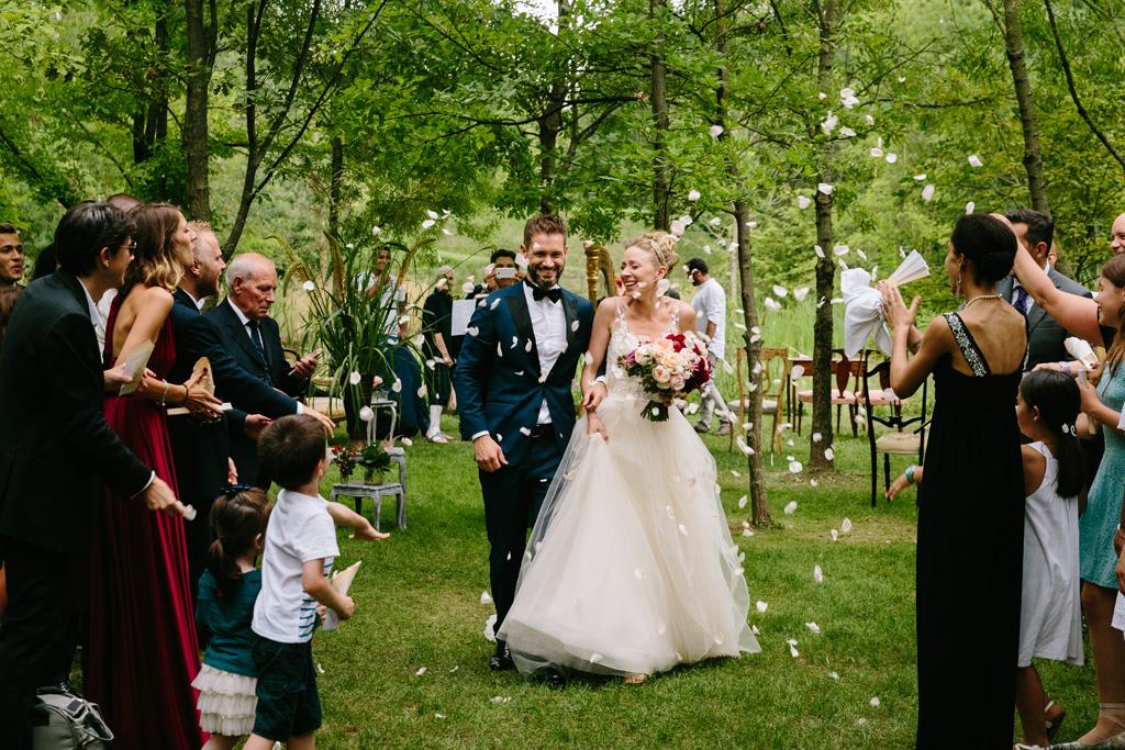 Gli sposi entusiasti immersi in una pioggia di petali di rose