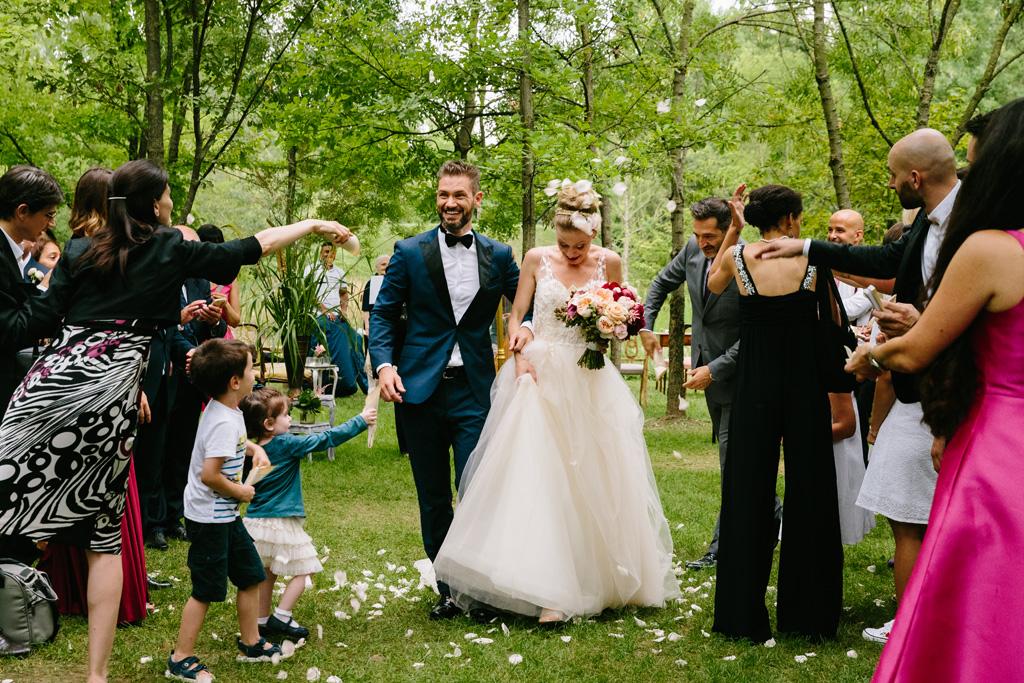 Gli invitati si divertono a tirare petali di rose sugli sposi