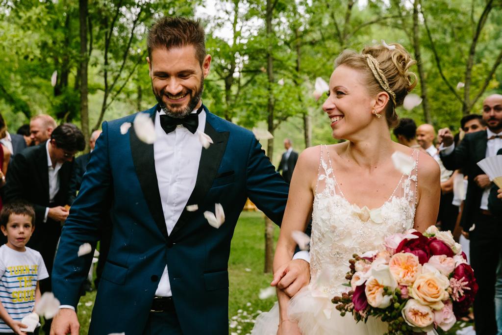 Gli sposi si guardano divertiti mentre cadono ancora petali di rose