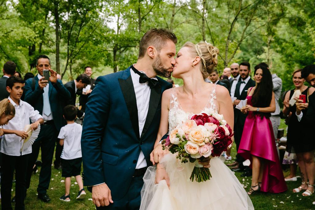 Gli sposi si baciano prima di lasciare il giardino del ricevimento