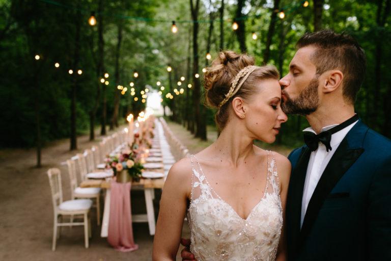Lo sposo bacia la sposa sulla fronte davanti al tavolo per la cena di nozze