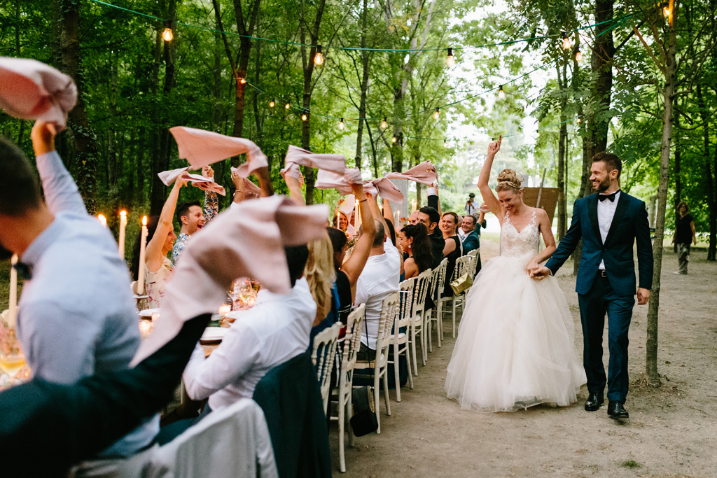 Gli invitati accolgono l'arrivo degli sposi agitando i tovaglioli rosa
