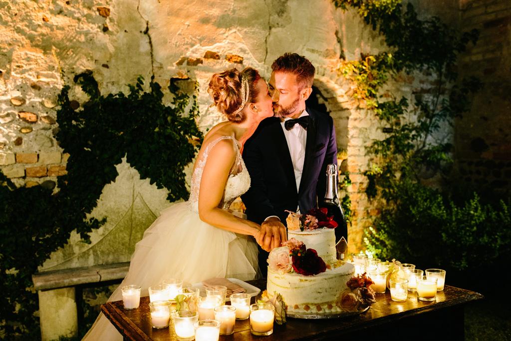 Gli sposi si baciano durante il taglio della torta