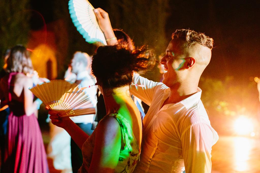 Una coppia di invitati balla e si fa aria con i ventagli bianchi