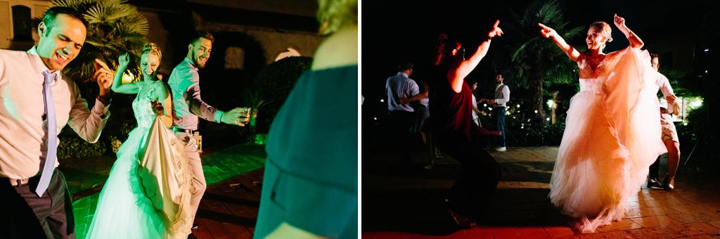 La sposa balla con gli invitati nelle luci colorate