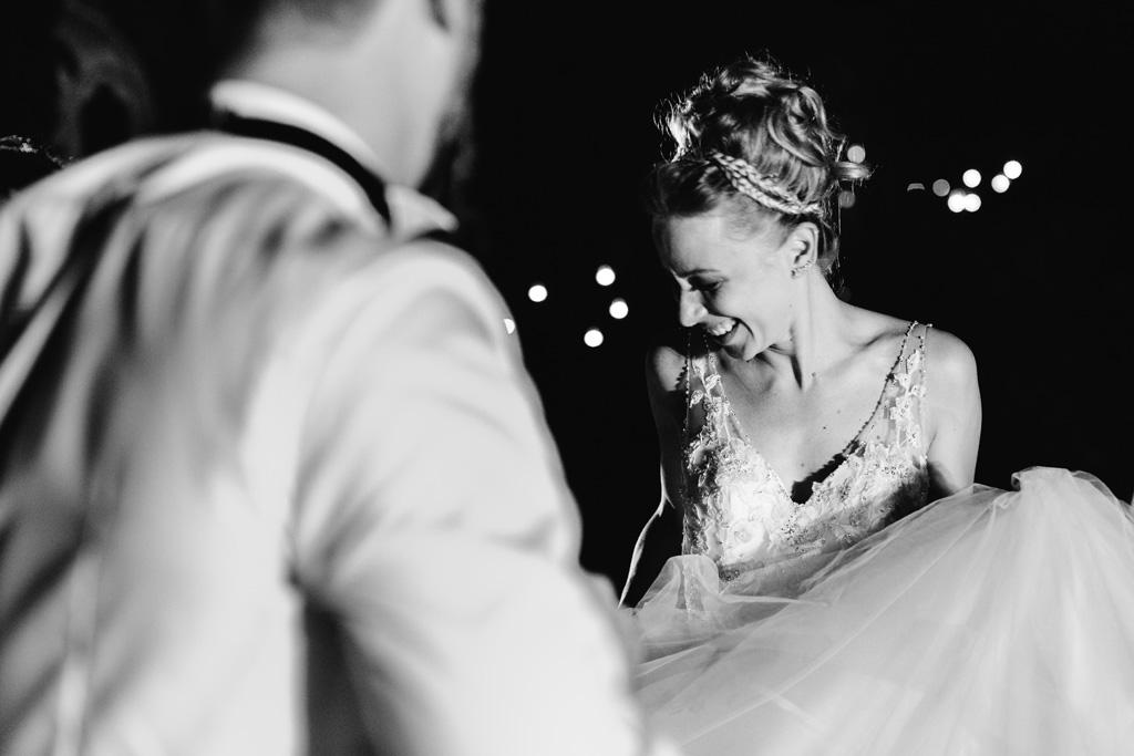 La sposa balla insieme al marito tenendo il vestito con le mani