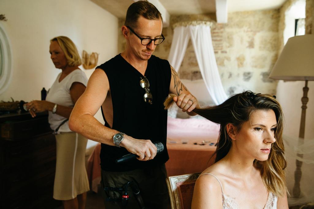 Il parrucchiere fa la piega ai capelli della sposa