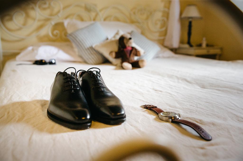 Scarpe e orologio dello sposo sul letto