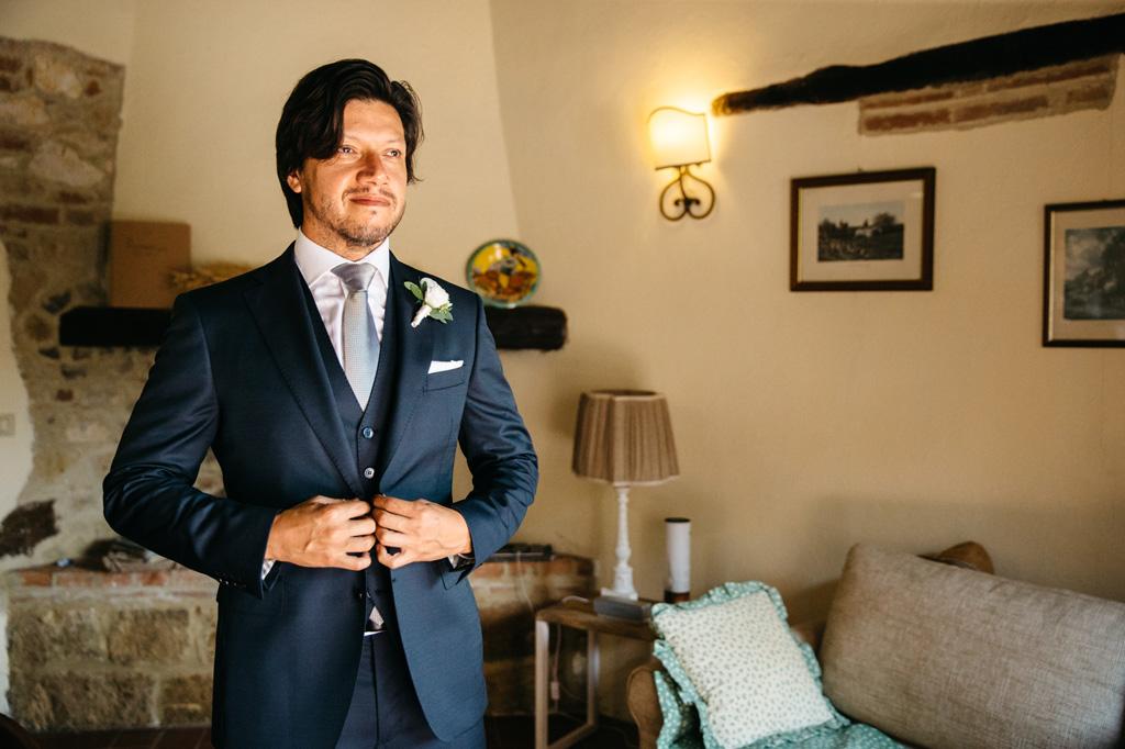 Lo sposo si allaccia i bottoni della giacca