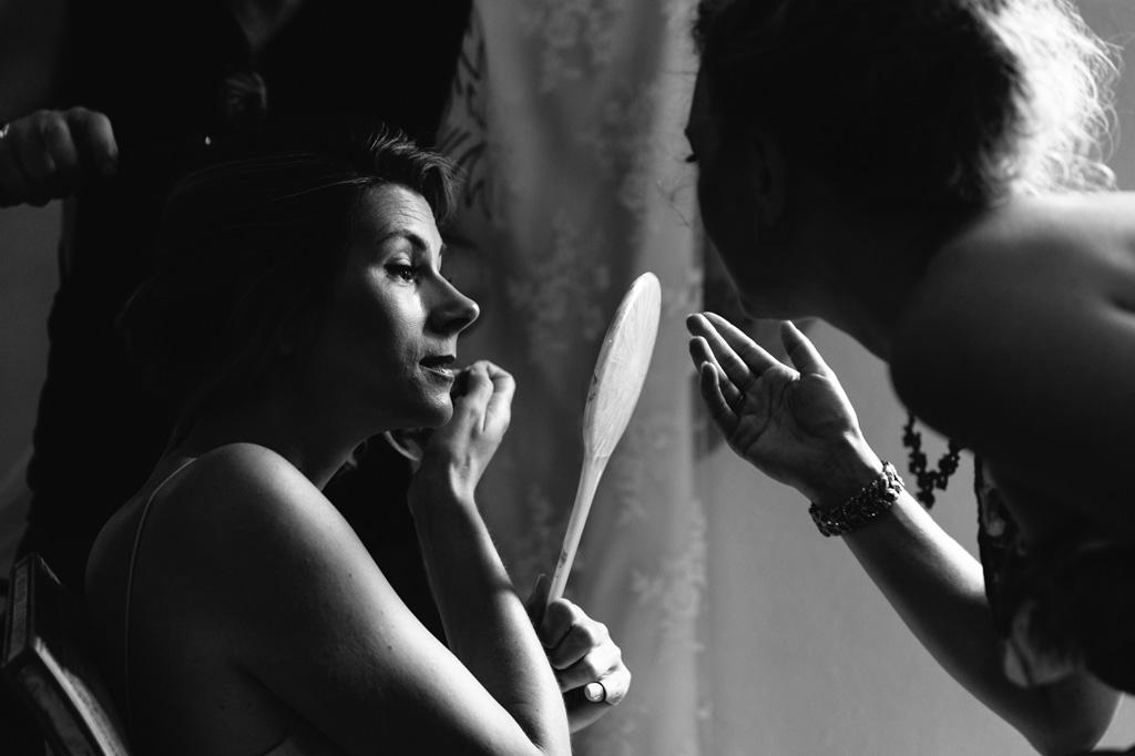 La sposa guarda il risultato finale del trucco allo specchio