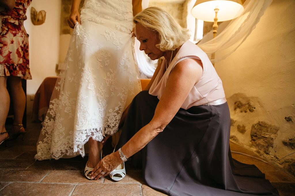 La mamma aiuta la sposa a infilare le scarpe