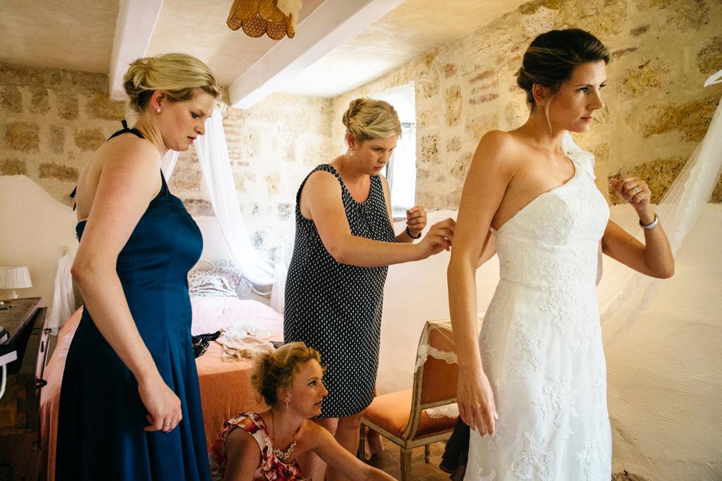 Le damigelle allacciano il vestito alla sposa