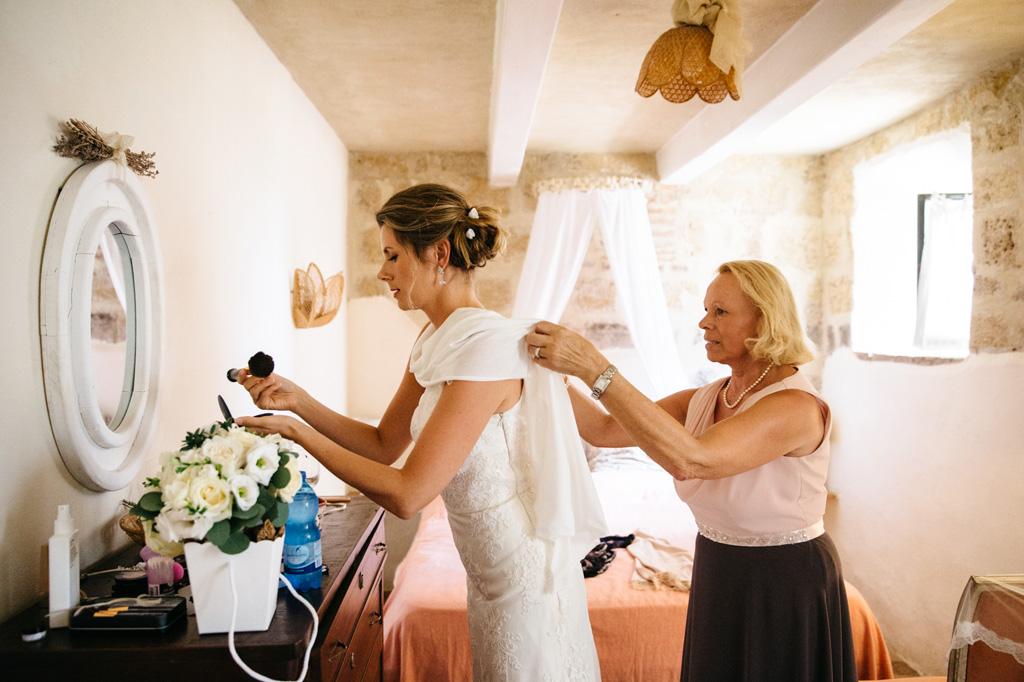La mamma sistema il vestito alla sposa mentre prende dei trucchi