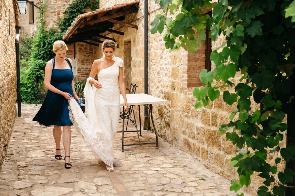 La sposa esce dalla stanza con la damigella e si dirige verso la macchina