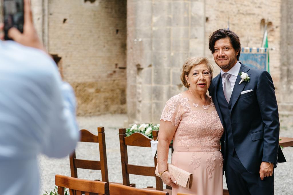 Lo sposo si fa fare una foto con la mamma prima della cerimonia