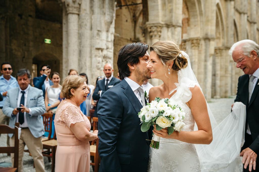 Lo sposo bacia la sposa sulla guancia mentre il padre le sistema il velo