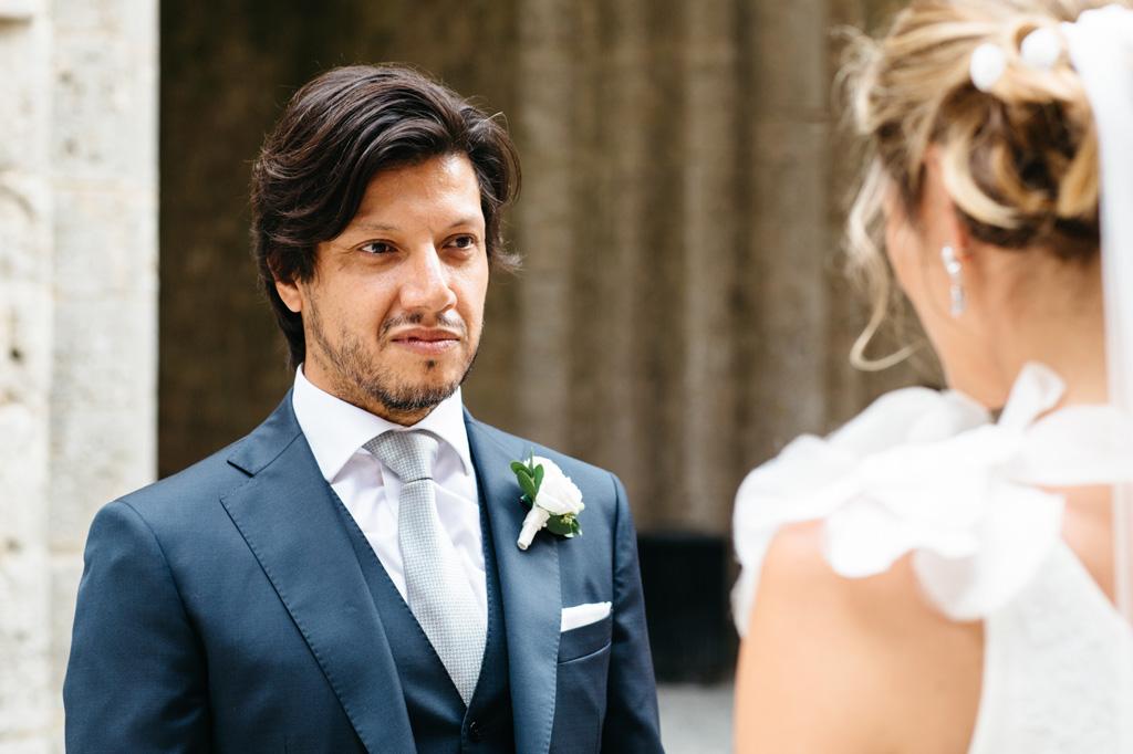 Lo sposo guarda la sposa con aria innamorata mentre lei pronuncia le sue promesse
