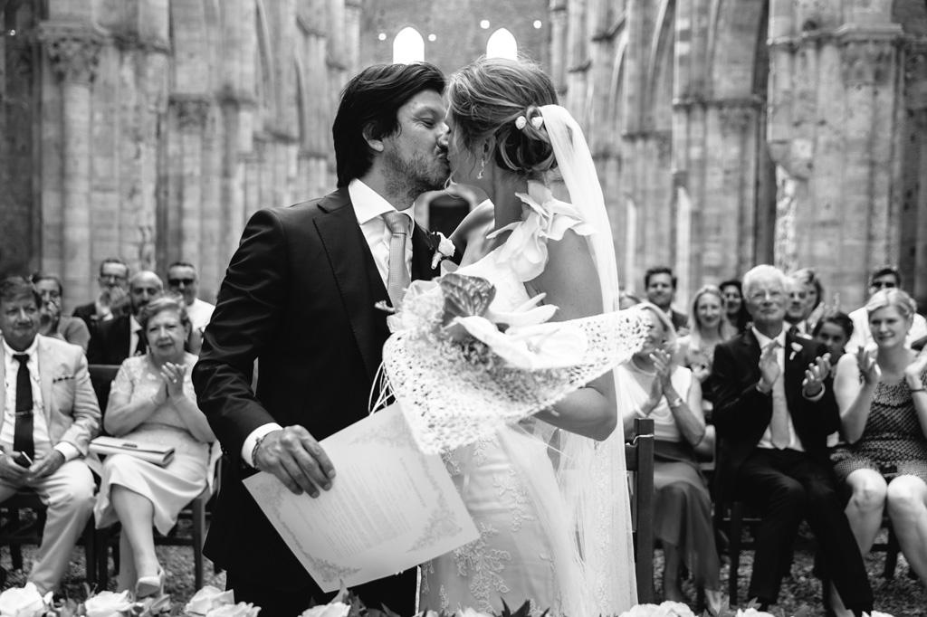 Il bacio degli sposi alla conclusione della cerimonia mentre gli invitati appaludono