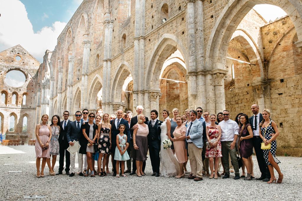 Foto di gruppo con sposi e invitati nell'Abbazia di San Galgano in Toscana