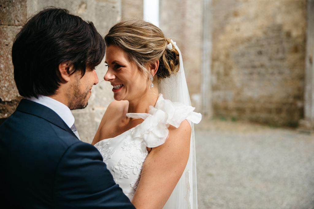 Gli sposi sia abbracciano e sorridono nell'Abbazia di San Galgano