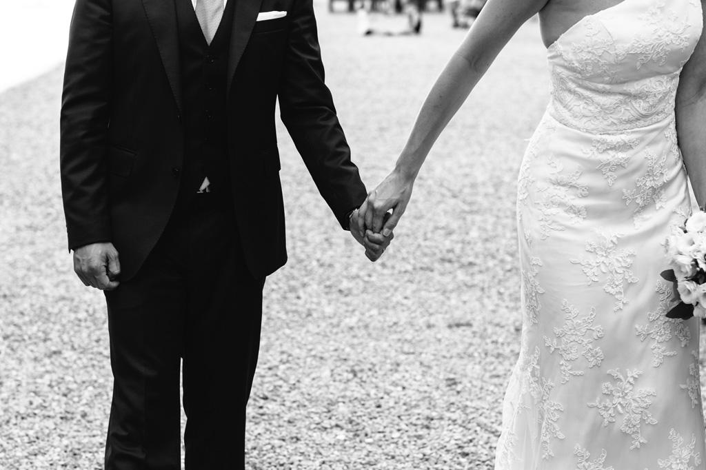 Gli sposi mano nella mano in bianco e nero