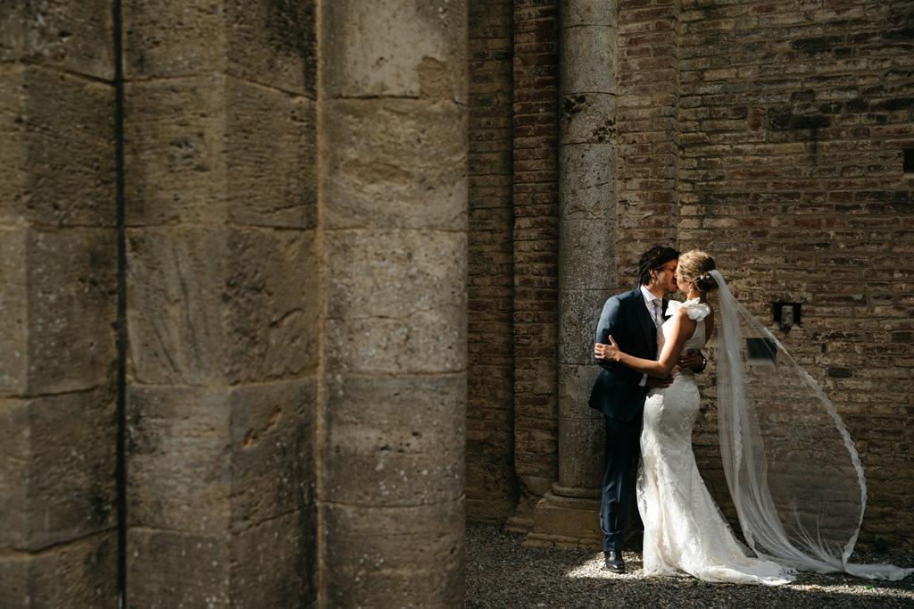Gli sposi si baciano in una zona illuminata dell'Abbazia di San Galgano