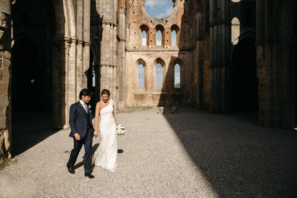 Gli sposi camminano mano nella mano nell'Abbazia di San Galgano ormai vuota