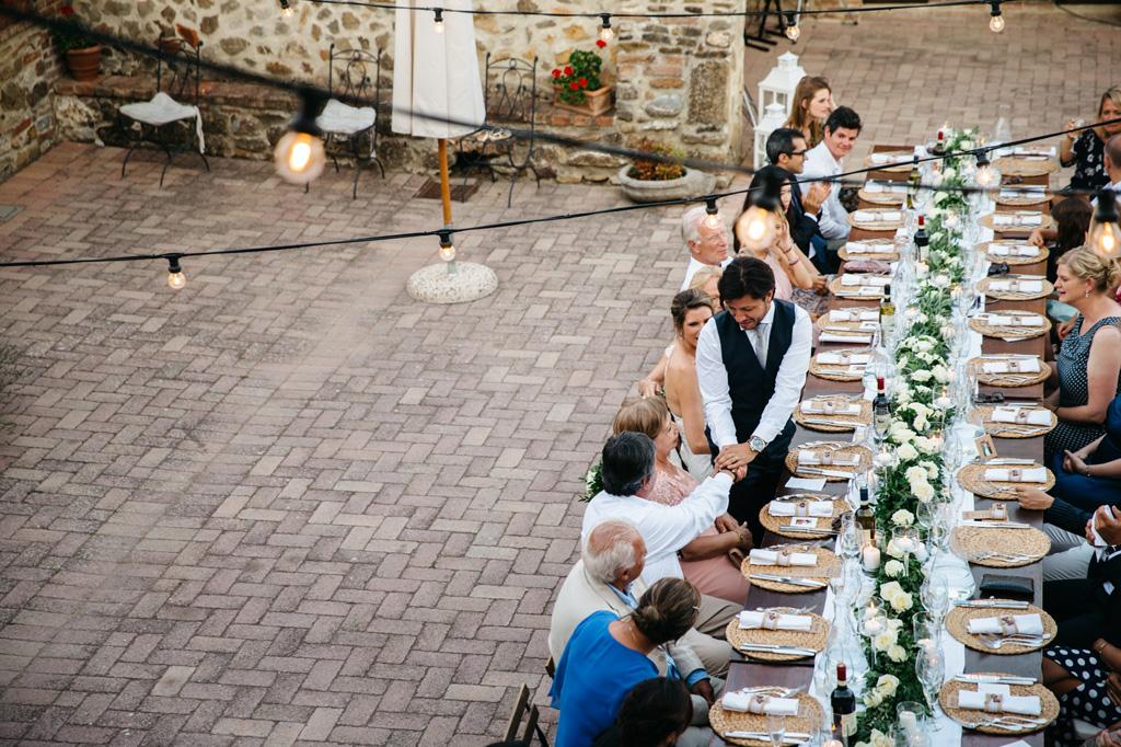 Lo sposo stringe la mano del padre al tavolo del ricevimento