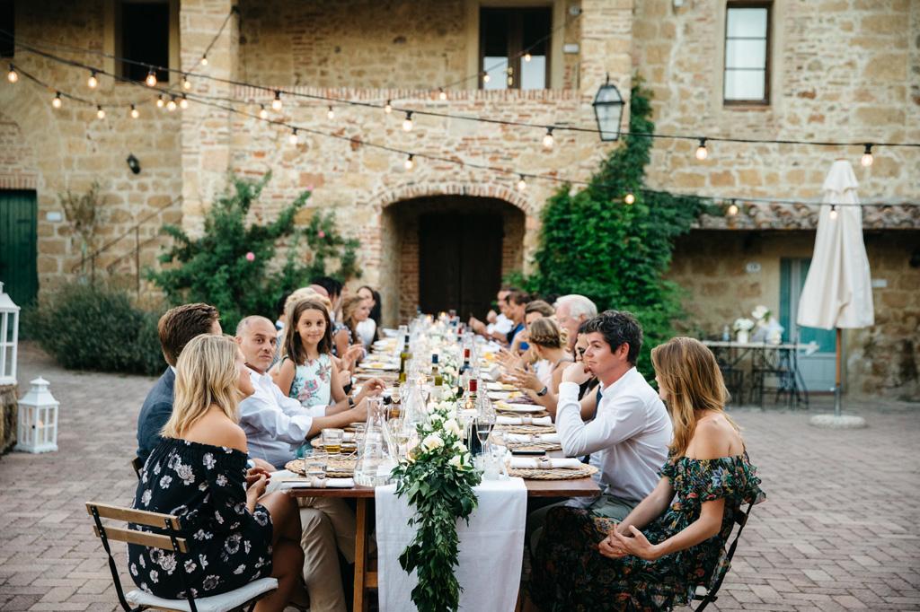 Gli invitati parlano tra di loro al tavolo durante la cena di nozze di Carlos e Catherine