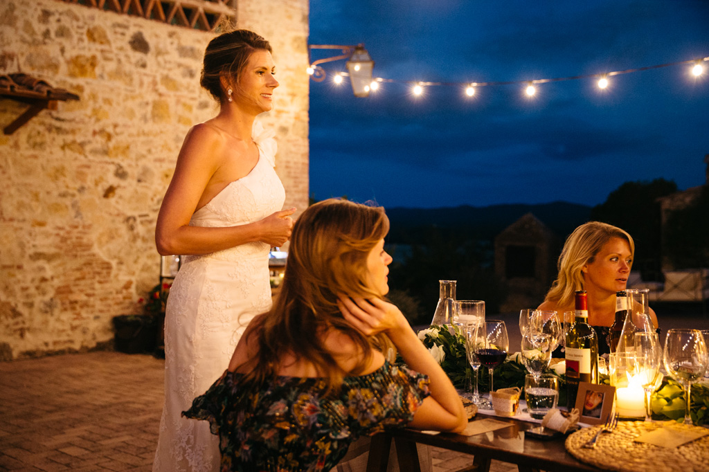 La sposa in piedi davanti al tavolo sorride agli invitati