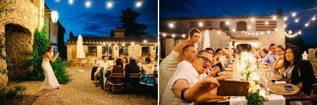 La sposa fa una foto a tutti gli invitati al tavolo la sera del ricevimento