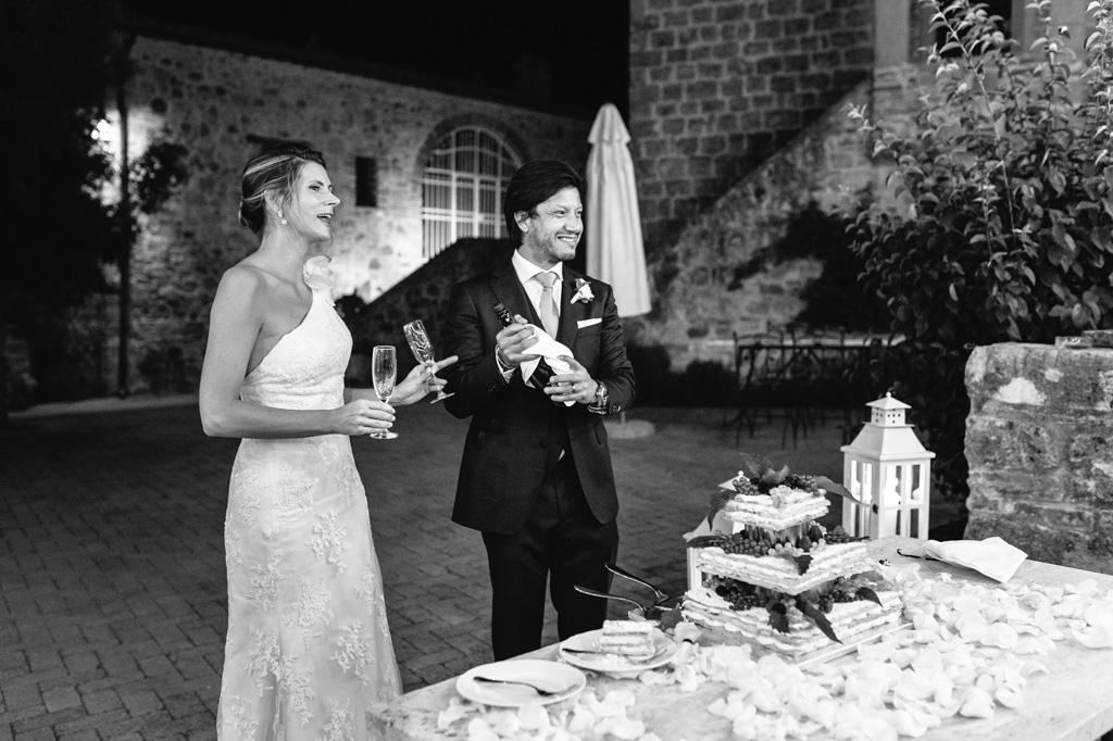 Lo sposo stappa lo champagne dopo il taglio della torta