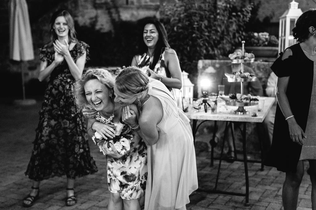 Le invitate si abbracciano divertite dopo il lancio del bouquet