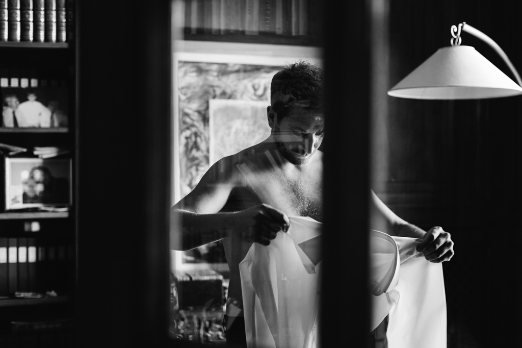 Lo sposo indossa la camicia nella sua casa di Como
