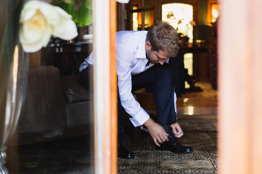 Lo sposo finisce di prepararsi mettendosi le scarpe