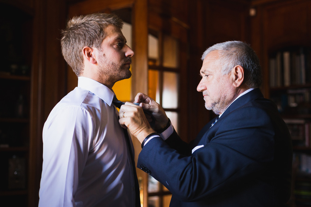Il padre aiuta lo sposo a fare il nodo alla cravatta