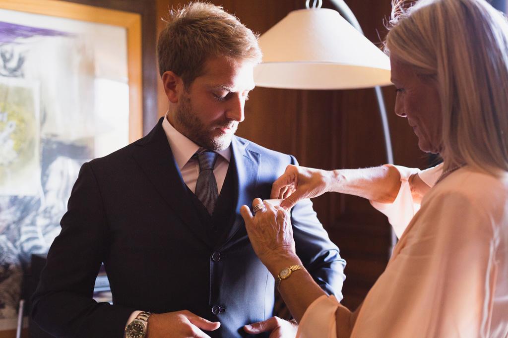 La mamma sistema i dettagli dell'abito dello sposo
