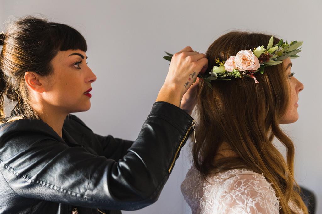 La parrucchiera definisce la coroncina di fiori e l'acconciatura