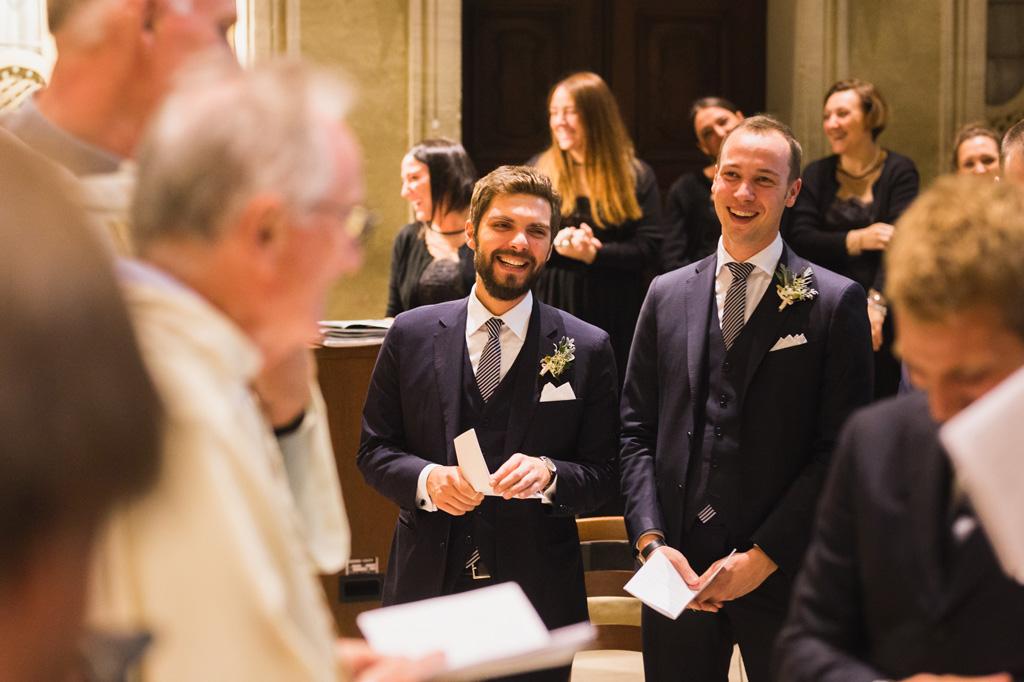 I testimoni dello sposo ridono durante la cerimonia in chiesa