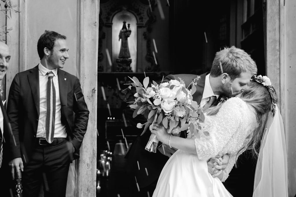 Lo sposo bacia la sposa fuori dalla chiesa sotto una cascata di riso portafortuna