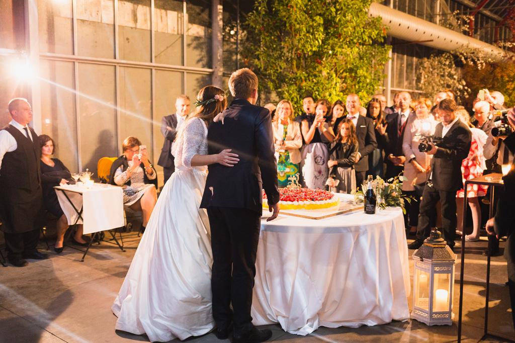 Gli invitati guardano gli sposi tagliare la torta