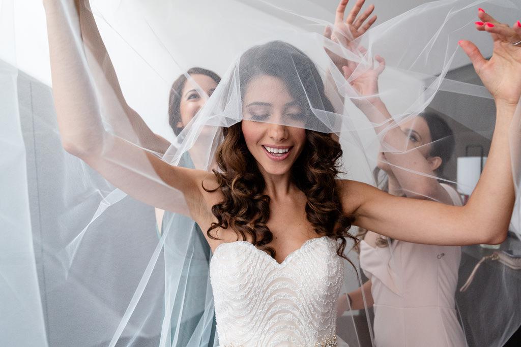 Le damigelle sistemano il velo alla sposa