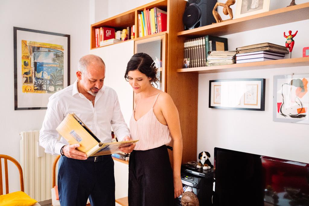 La sposa e il padre guardano un album di fotografie nella casa di Milano