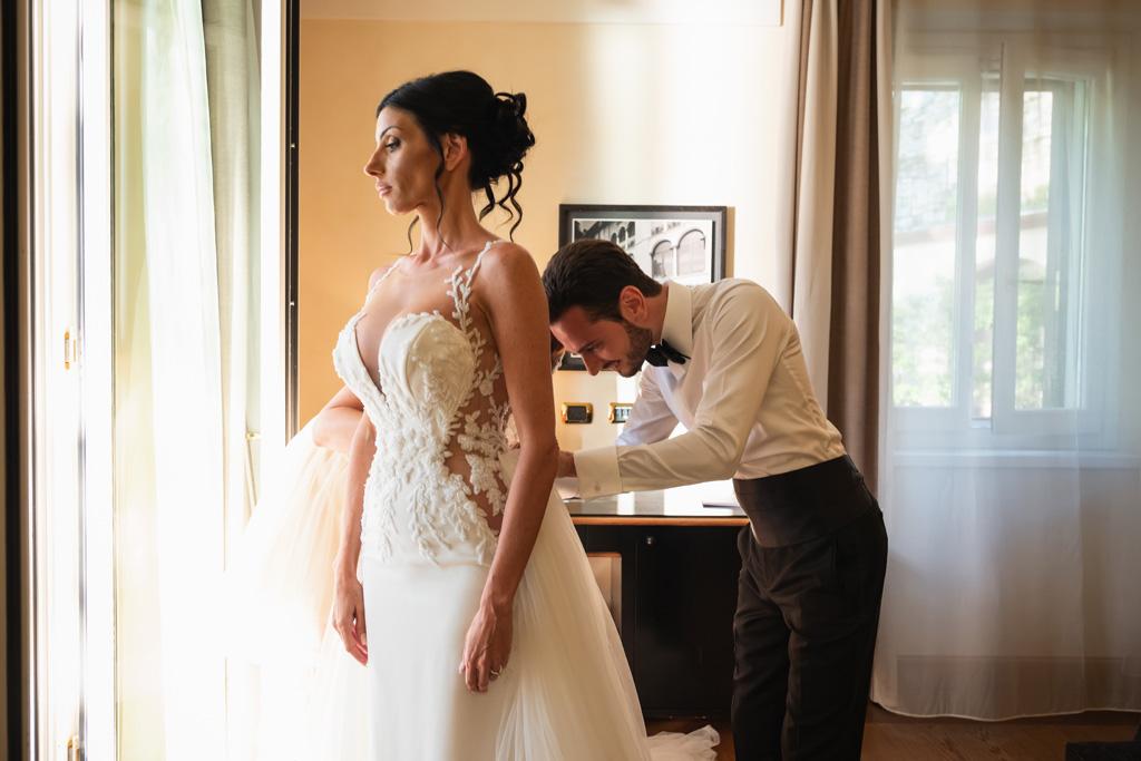 Lo sposo allaccia il vestito alla sposa