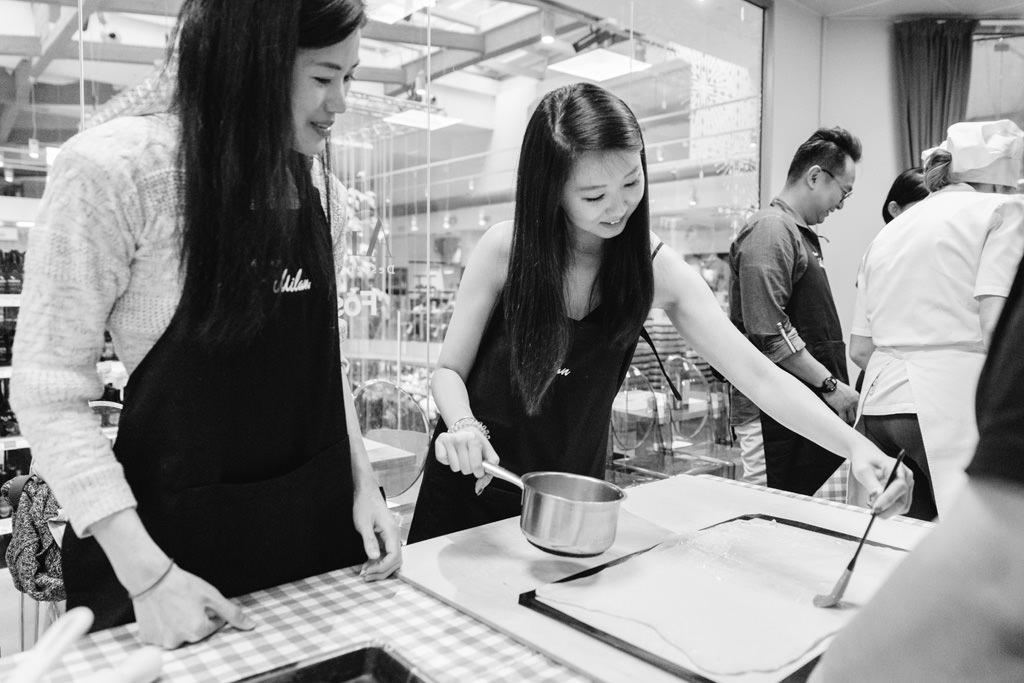 Le invitate si divertono in cucina ritratte dal fotografo di eventi di team building aziendali Alessandro Della Savia