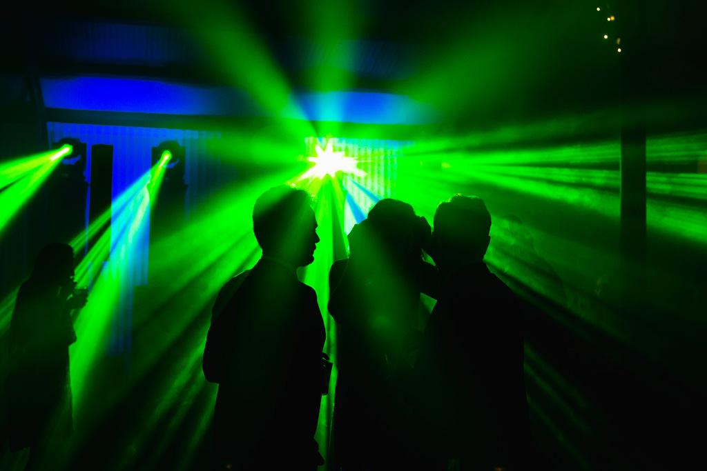 Gli invitati si scatenano in pista sotto le luci stroboscopiche in uno scatto di Alessandro Della Savia, servizi fotografici per feste e cene aziendali