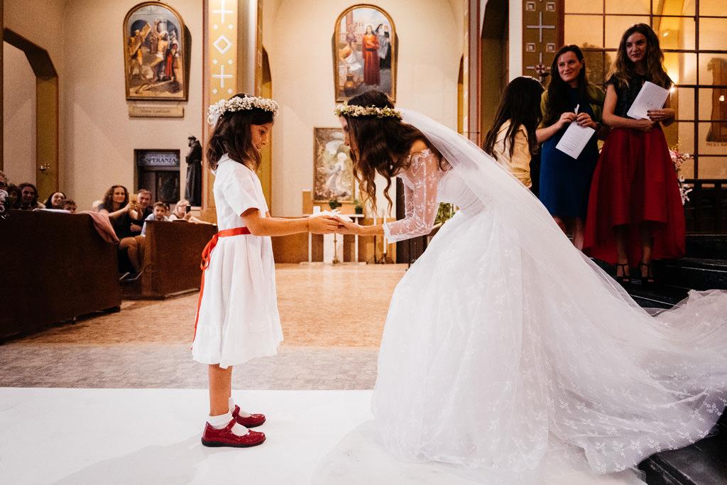 Una damigella porta le fedi alla sposa