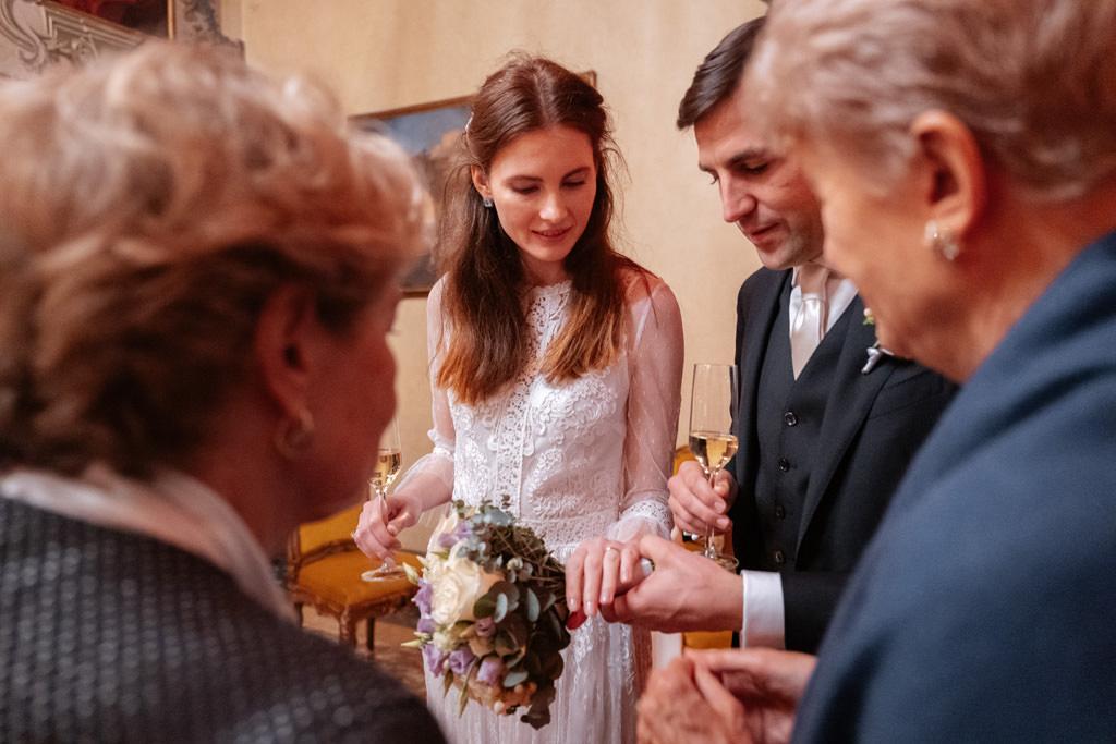 Gli sposi mostrano le fedi alle mamme