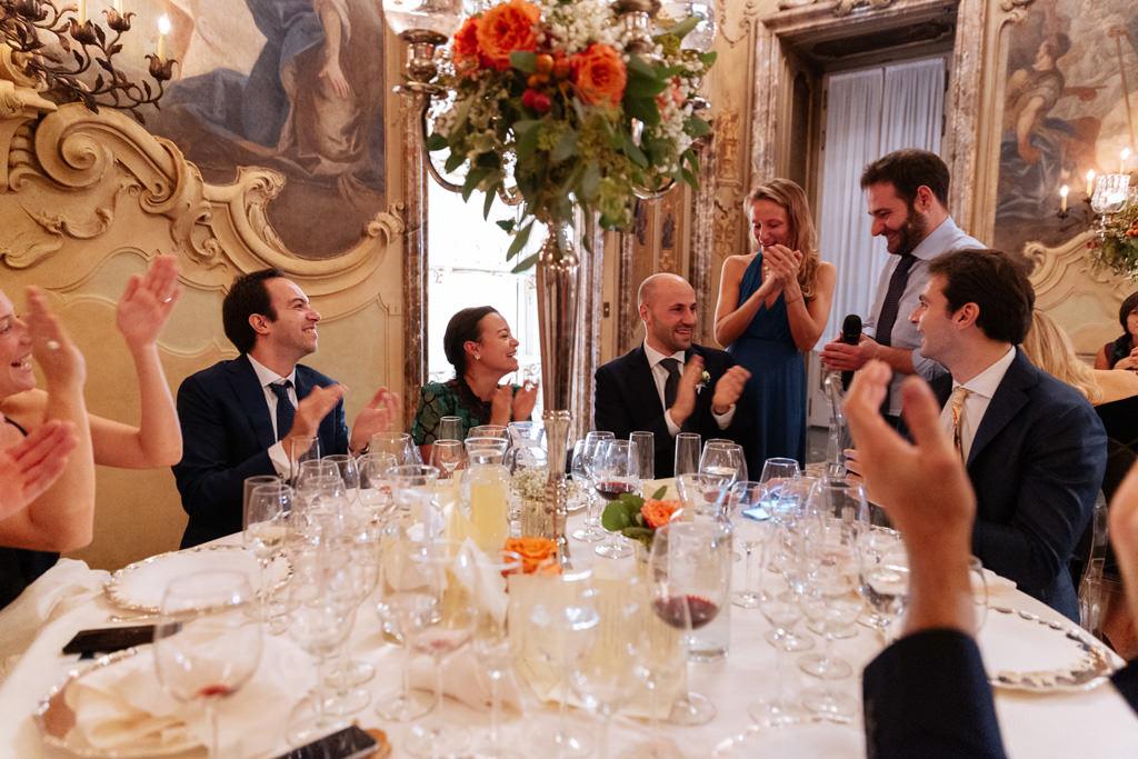 Gli invitati applaudono dopo il discorso del fratello dello sposo